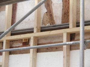 Anschrauben von Hölzern zum lot- und fluchtgerechten Ausgleich der enorm schiefen Fassade, Möglichkeit der Verlegung von neuen Versorgungsleitungen über die Fassade
